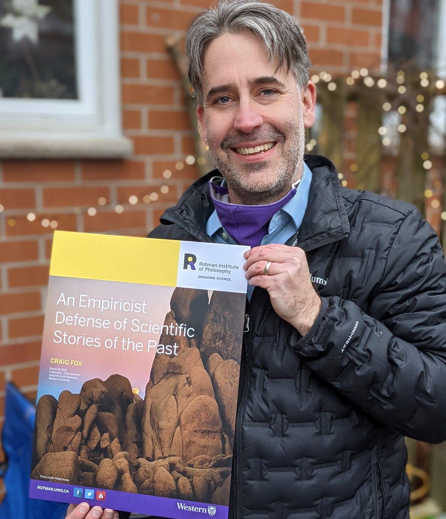 Craig Fox holding his talk's poster