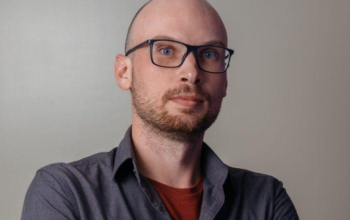 Bartek Chomanski in front of grey background