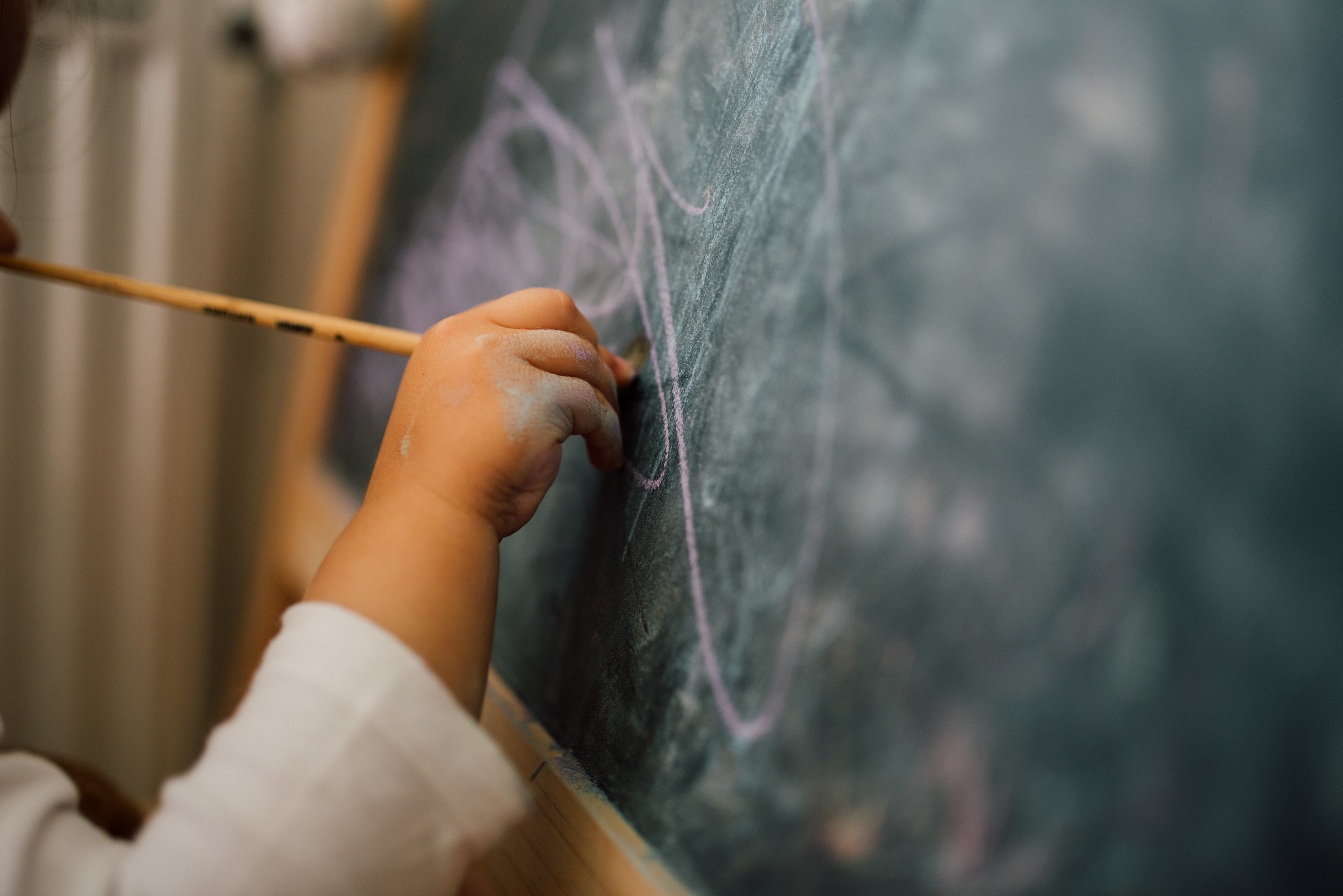 Child scribbling on a chalkboard