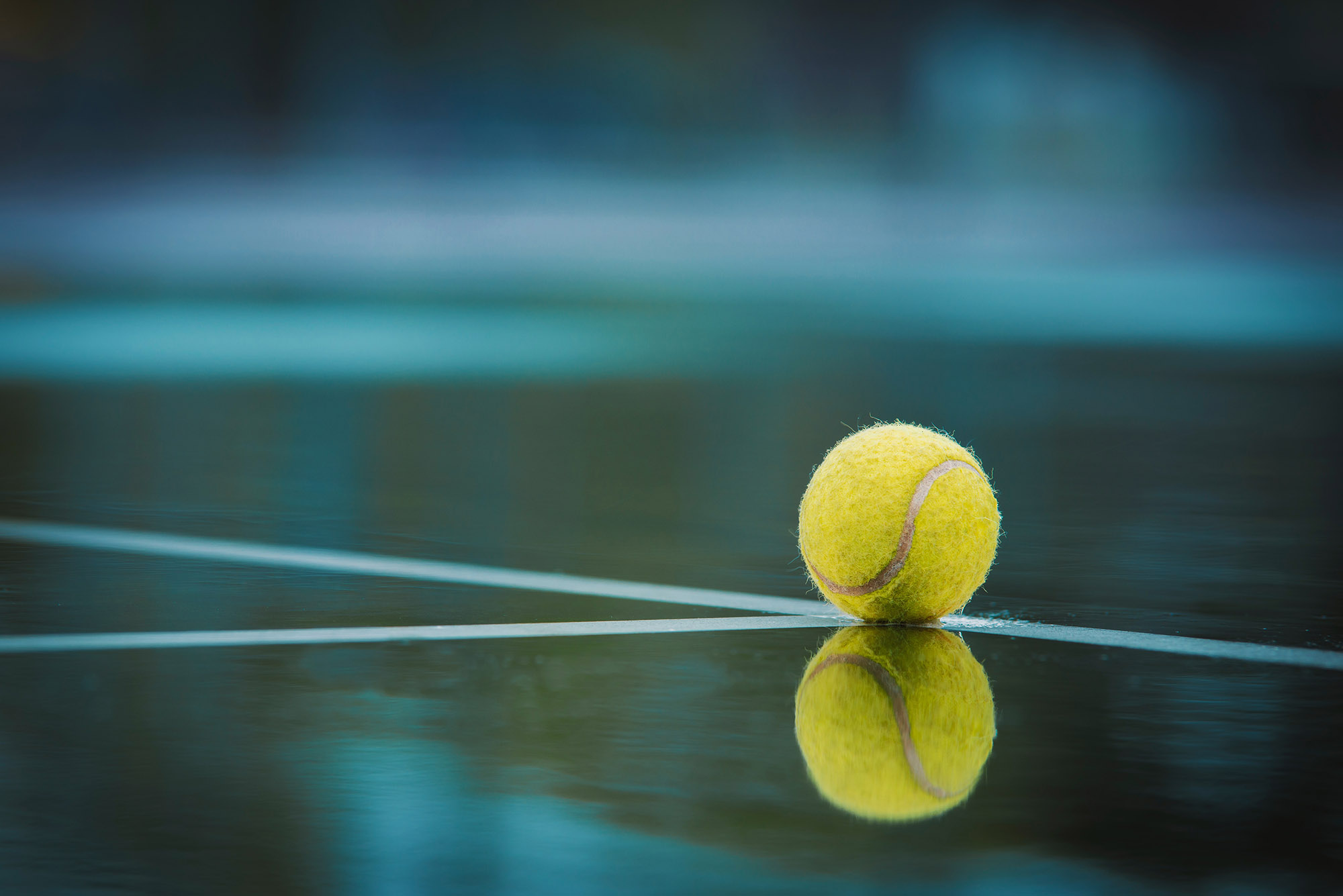 Tennis ball with reflection on surface of tennis court.